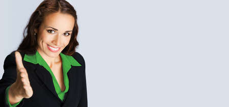 Businesswoman in confident black suit and green blouse, giving hand for handshake, empty copy space place for some text, advertising or slogan, over grey background. Business concept studio photo. Stock fotó