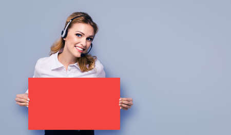 Call Center Service. Customer support or sales agent. Businesswoman or caller phone operator holding empty red colour paper board banner with copy space. Helping, answering consulting. Isolated on grey