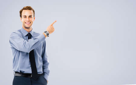 Businessman showing something, standing against grey color background. Copy space area for some text. Success in business, job and education concept. Pointing confident man at studio. Stock fotó