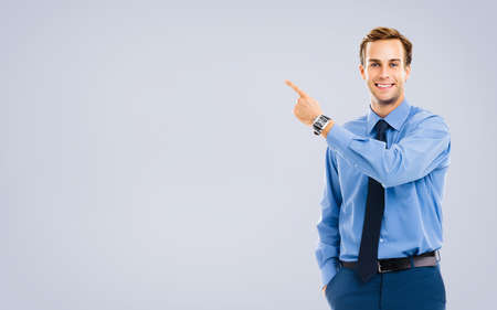 Portrait image of businessman showing something, standing over grey color background. Copy space area for some text. Success in business or education concept. Pointing man in blue confident clothing. Imagens