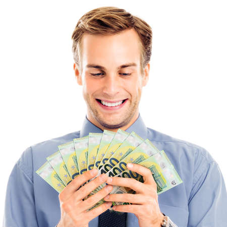 Smiling businessman holding money, looking at euro cash banknotes, isolated over white background. Success in business or finance concept. Happy man in grey confident clothing at studio. Square.