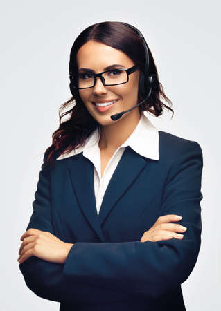 Portrait image of happy smiling customer support female phone operator in eye glasses and headset, over grey color background. Consulting and assistance service call center. Business woman at studio.
