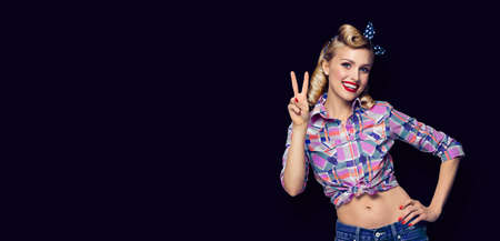 Pin up girl. Excited happy pinup woman showing two fingers or victory gesture hand sign. Retro and vintage concept. Black background. Copy space for advertise slogan, sign or text.