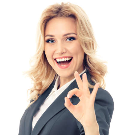 Happy smiling businesswoman in grey confident suit, showing okay hand sign gesture, against white background. Caucasian blond model in business success concept. Square composition image.