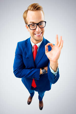 OK! Portrait of funny happy businessman in glasses, blue suit and red tie, showing okay gesture or zero, over grey background. Business concept.