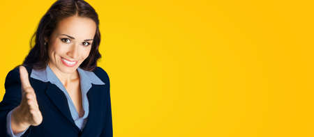 Businesswoman in confident black suit and blue blouse, giving hand for handshake, copy space place for some text, advertising or slogan, over yellow background. Business concept studio photo.