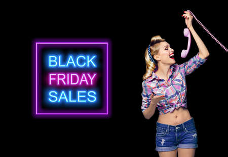 Young happy pinup woman holding telephone tube. Excited pin up girl, profile. Blond model at retro fashion and vintage concept. Dark background. Black Friday sales neon light sign.