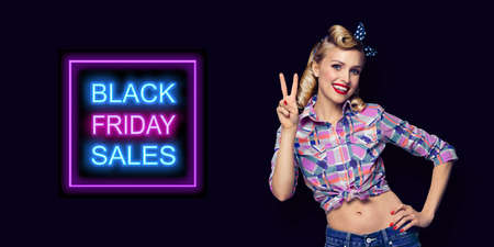 Pin up girl. Excited happy pinup woman showing two fingers or victory gesture hand sign. Retro and vintage concept. Dark background. Black Friday sales neon light sign.