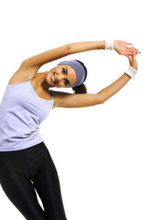 Happy smiling african american or latinos woman in sportswear doing stretching exercise or youga moves, isolated over white. Young sporty model at studio. Health, beauty and fitness concept.