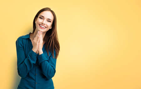 Happy gesturing smiling young brunette woman in casual smart blue clothing, pressing palms together, isolated over yellow background, with copy space for some slogan or text message.