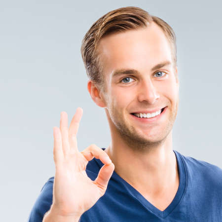 Portrait of cheerful young man showing okay ok gesture, isolated over grey background. Emotions and success studio concept. Square composition.