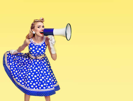Happy excited woman holding megaphone, dressed in pin up style blue dress in polka dot and white gloves, on yellow background. Beautiful blond girl in retro fashion vintage studio picture.