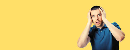 Unhappy shocked panic man, isolated over yellow color background. Emotions and unsuccessful concept. Excited male model with rise up hands, blue casual clothing at studio.