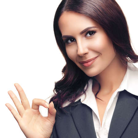 Happy smiling beautiful young businesswoman in gray confident suit, showing okay gesture, isolated against white background. Square composition image.