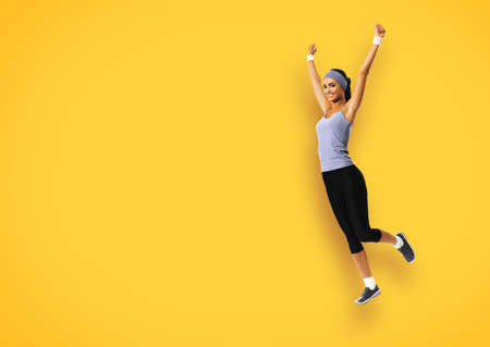 Full body of happy woman jumping or doing fitness exercise, isolated over yellow color background. Fit girl with raised up hands, in sportswear, at studio image.