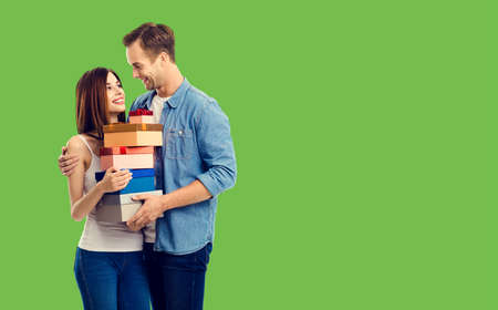 Love, relationship, dating, flirting, lovers, romantic concept - happy young couple holding gift boxes, close to each other. Green background. Copy space.