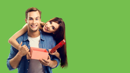 Love, relationship, dating, flirting, lovers, romantic concept - happy couple opening gift box. Green color background. Copy space for some text.