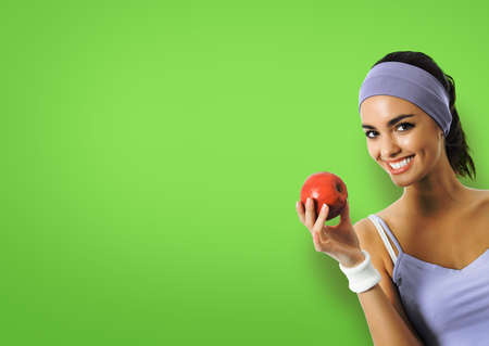 Portrait of african american woman in sportswear with red apple, isolated over green color background. Sporty girl at studio shot. Health, dieting and fitness gym center concept. Zdjęcie Seryjne - 162219374
