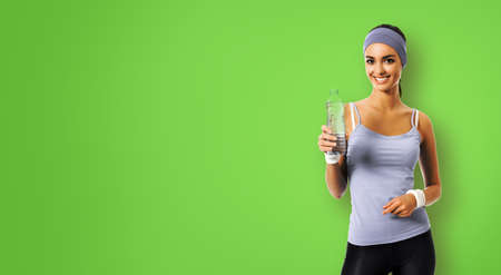 Happy smiling african american woman in grey sportswear with bottle of water, isolated over green background. Sporty attractive girl at studio. Fitness gym concept.