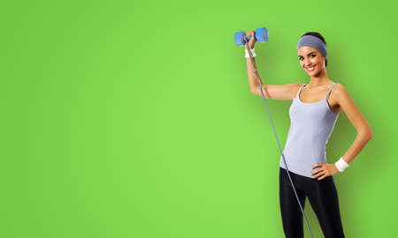 Happy smiling african american woman doing exercise with growth and dumbbell, isolated over green color background. Young sporty model at studio shot. Health, beauty and fitness concept.
