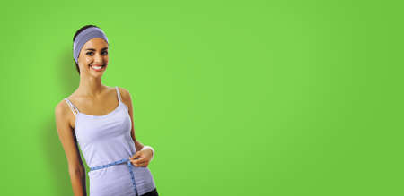 Woman in sportswear measuring waist with a tape measure, isolated over green color background. Sporty african american girl at studio. Health, beauty and fitness gym center concept.