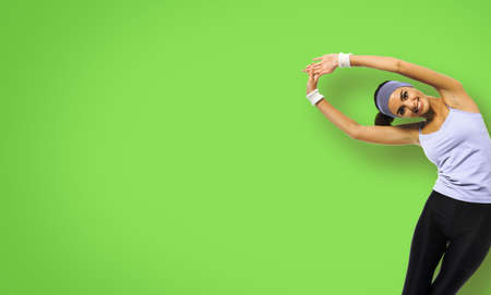 Happy smiling african american woman in grey sportswear doing stretching exercise or youga moves, isolated over green background. Young sporty model at studio. Health, beauty and fitness concept.