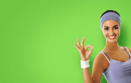 Young happy african american woman in sportswear showing okay hand sign gesture, isolated over green color background. Sporty model at studio shot. Health, beauty and fitness concept. Stok Fotoğraf