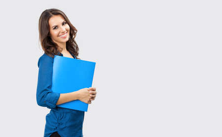Portrait of happy smiling brunette businesswoman with blue folder, with blank copy space area for slogan or text, posing at studio against grey background