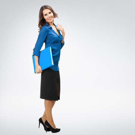 Full body portrait of young happy smiling brunette businesswoman with blue folder, with copy space area for slogan or text, posing at studio against grey background