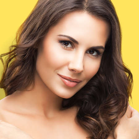 Portrait of beautiful young woman, isolated over yellow color background. Brunette girl in studio picture. Beauty and health concept. Square composition.