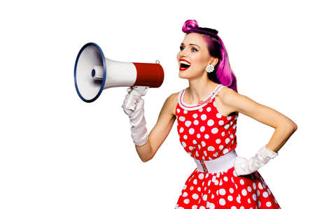 Beauty red haired woman holding megaphone, shout something. Girl in pin up style dress in polka dot, isolated over white background. Caucasian model posing in retro fashion vintage concept. Archivio Fotografico