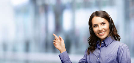Contact Call Center Service. Customer support, female sales agent. Caller or answering phone operator or businesswoman in headset. Woman showing empty copy space area. Blurred modern office interior.