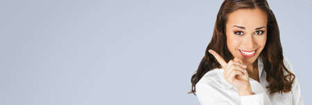 Close up portrait of happy smiling woman in white confident blouse, showing pointing at copy space for text or imaginary. Business concept. Grey color background. Brunette businesswoman. Wide image.