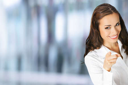 What about You? Happy smiling woman in confident clothing pointing finger at viewer, copy space. Business concept. Blurred modern office interior background. Brunette businesswoman, indoors.