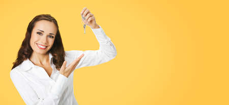 Happy smiling young businesswoman or real estate agent showing keys from new house. Portrait of brunette woman at studio, orange yellow color background with copy space area. Wide composition.