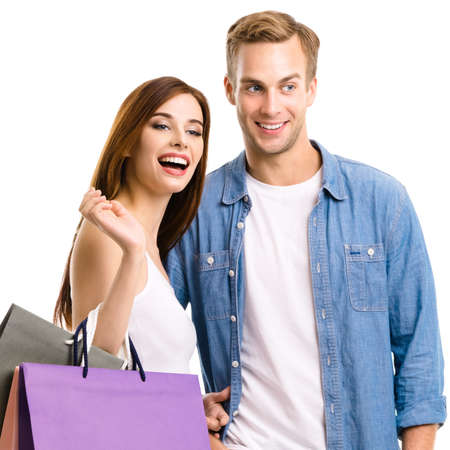 Happy couple with shopping bags, standing close to each other with smile. Caucasian models in love, holiday sales, shop, retail, consumer concept, isolated on white background. Square.