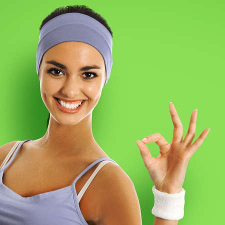 Young happy african american woman in sportswear showing okay hand sign gesture, isolated over green color background. Sporty model at studio shot. Health and fitness concept. Square composition. Stock Photo
