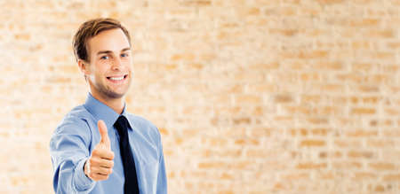 Portrait of smiling confident businessman showing thumbs up like hand sign gesture, over brown bricks loft wall background. Happy confident man gesturing. Copy space area. Success in business.