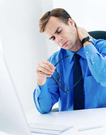 Image of frustrated, exhausted or tired business man in confident blue shirt, with glasses, touching neck. Businessman with computer at office.