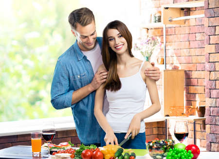 Image of happy amazed amorous couple cooking together at domestic kitchen with vegetarian healthy fresh food. Young family and healthy diet eating concept.