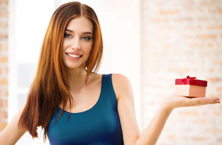 Image of young smiling woman with gift, indoor. Beautiful brunette girl in casual blue dress - celebration and holiday sales concept.