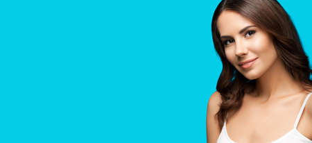 Portrait of happy smiling beautiful woman in white casual tank top, over aqua blue background. Brunette girl at studio. Beauty concept. Wide horizontal composition image with copy space.