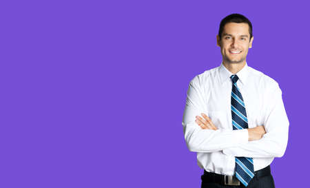 Portrait of happy smiling young brunette businessman in white shirt and blue tie, standing in crossed arms pose, isolated over violet purple colour background with copy space. Confident business man.