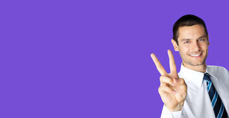 Businessman in white confident shirt and tie showing two fingers or victory gesture, over violet purple color background. Happy smiling gesturing brunette man at studio. Business ad concept. Standard-Bild