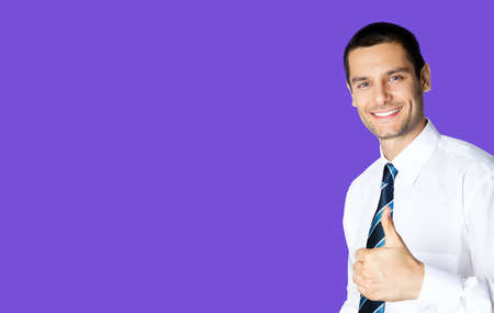 Portrait of smiling businessman in white shirt and tie, showing thumb up like hand sign gesture, isolated over violet purple colour background. Happy confident man gesturing. Success in business. Standard-Bild