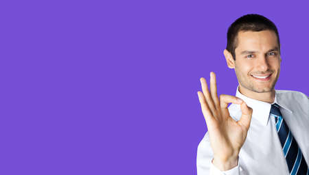 Portrait of smiling businessman in white shirt and tie, showing thumb up like hand sign gesture, isolated over violet purple colour background. Happy confident man gesturing. Business success concept.