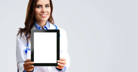 Happy smiling female doctor showing tablet pc touchpad with copy space for imaginary or text, over grey background. Medical care concept. Selective focus.