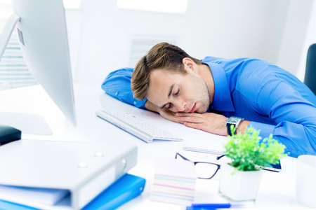 Image of very tired businessman in blue shirt, sleeping at workplace, with computer, indoors. Business, job and overworking concept. Standard-Bild