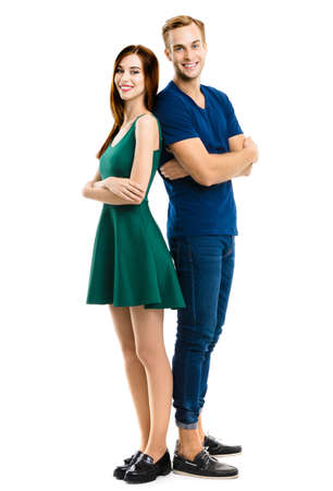 Image of smiling attractive couple. Full body length portrait of standing back to back models at happy in love studio concept, isolated over white. Man and woman posing together.