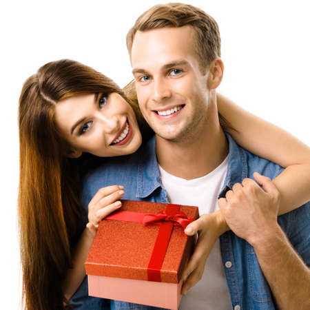 Happy smiling couple with gift box, close to each other and looking at camera with smile. Caucasian models in love, relationship, dating concept, isolated against white. Square.